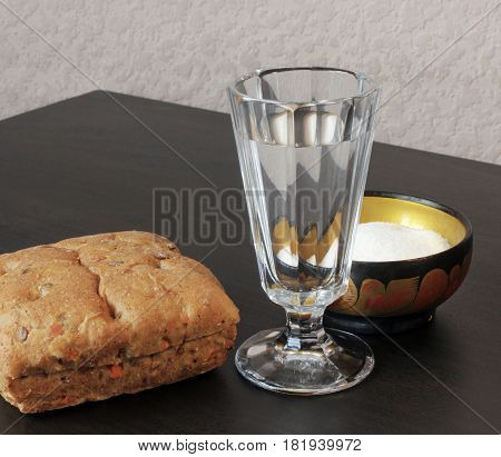 Closeup view of vintage shot glass for vodka fresh bread bun and beautiful vintage saltcellar on black wooden table.