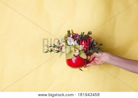 Hand holds a small red vase with flowers on a yellow background, space for text
