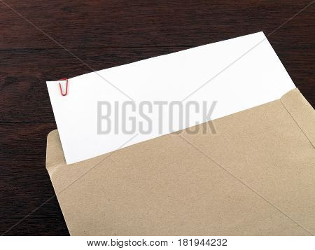 white paper with paperclip in brown envelope on dark brown wooden desk floor, blank document