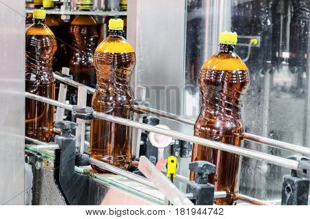 Plastic bottles with beer on the conveyor. Brewing production. Abstract industrial background.