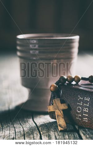 Rosary beads, holy bible and cup of wine on wooden table.