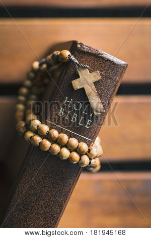 Rosary beads and holy bible on wooden table. Top view.