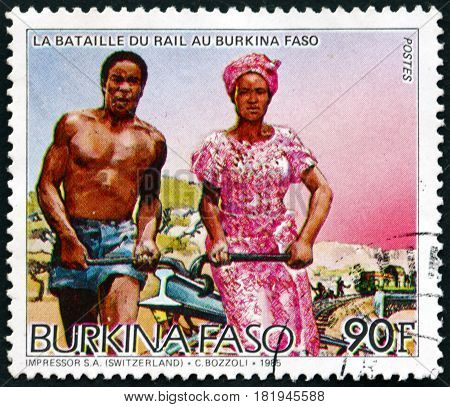 BURKINA FASO - CIRCA 1986: a stamp printed in Burkina Faso shows Man and Woman Carrying Rail Railroad Construction circa 1986