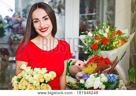 Beautiful brunette in red dress buys a bouquet of flowers in flower shop