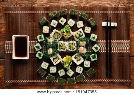 Great ornament of vegetarian sushi rolls set served on brown straw mat, flat lay. Japanese traditional cuisine, food art, culinary masterpiece.
