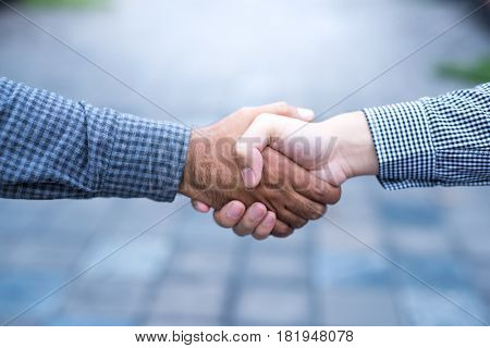 Men shaking hands. Top view of two men shaking hands while standing on the paving tiles cement brick floor.