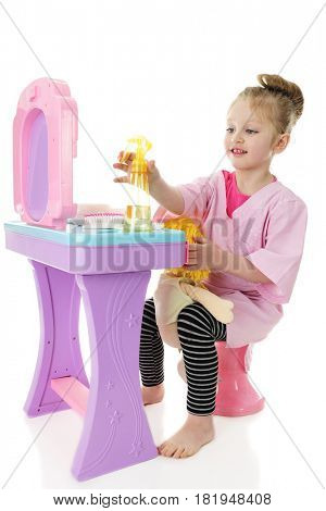 An adorable preschool girl playing hair stylist with her doll. She's reaching for a spray bottle on her hairdresser station.  On a white background.