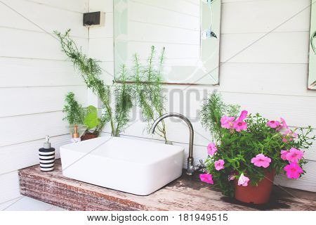 Washbasin with pink flowers in home garden White and beautiful concept