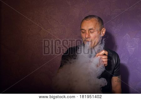 Serious Tattooed Man Smoking Vaporizer, Releases Clouds Of Vapor