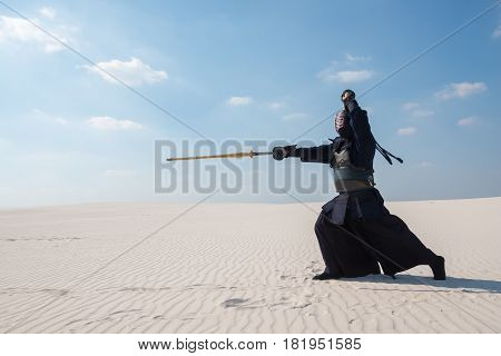 Man In Traditional Armor For Kendo Makes A Deep Lunge With His Sword