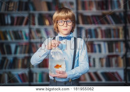 Little child with goldfish in library