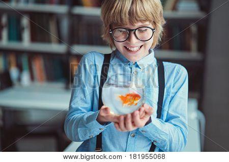 Smiling boy with goldfish indoors