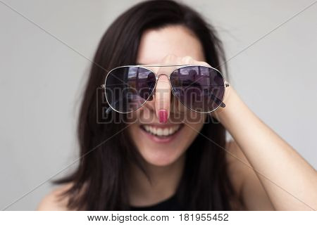 A beautiful girl trying on sunglasses. She's having fun and fooling around. Pointing finger like a huge nose
