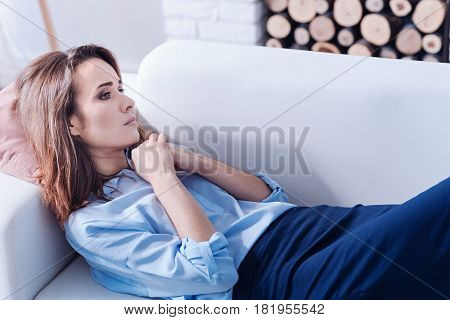 Chronic depression. Beautiful sad young woman lying on the sofa and holding her hands together while suffering from chronic depression