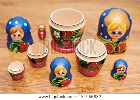 Many open Russian nesting dolls lying on a wooden table