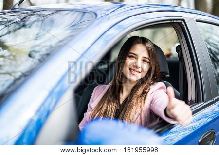 Happy Businesslady In Dark Red Shirt Driving Her Car And Showing Thumb Up. Smiling Lady Taking Steer