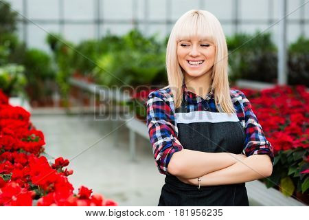 Portrait of a florist woman standing in the garden center, and smiling. Job florist in a greenhouse.