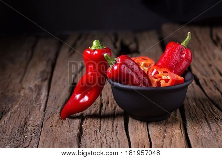 Red Chilly Pepper On Wooden Black Background. Red Hot Chili Peppers.