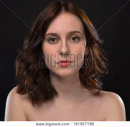 Brunette woman with nude shoulders on black background