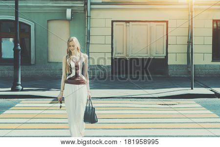 Smiling tall beautiful adult woman passing crosswalk on summer springtime cheerful blonde lady with bag on pedestrian crossing with copy space for your advertising text message or promotional content