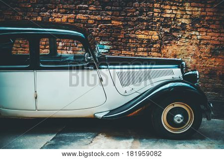 Side view of noname luxury retro vintage car with curved forms black and white colours in front of orange grunge brick wall