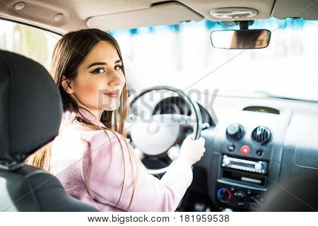 Woman In Car Indoor Keeps Wheel Turning Around Smiling Looking At Passengers In Back Seat.