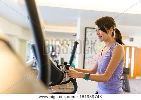 Woman training on Elliptical machine in gym