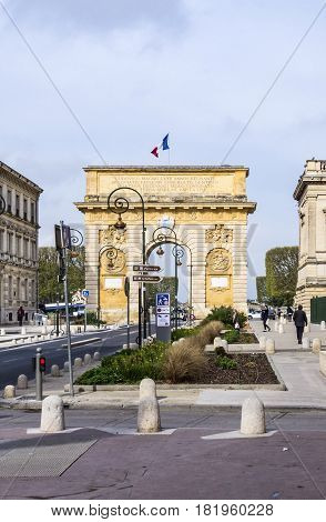 Arc De Triomphe In Montpellier, Dating From 1692, With Surrounding Buildings, People And Traffic Sig