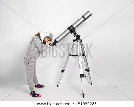 Happy child girl dressed in an astronaut costume looks through a big telescope.