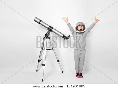 Happy child girl dressed in an astronaut costume standing beside the telescope.