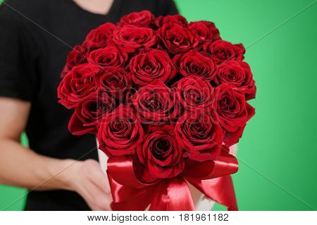 Man In Black T Shirt Holding In Hand Rich Gift Bouquet Of 21 Red Roses. Composition Of Flowers In A