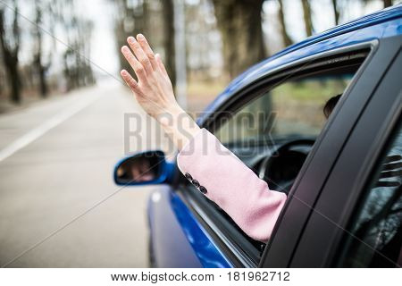 Woman Sticking Arm Out Of The Car Window On Roadtrip. Female Driver Hand Feeling The Air And Freedom
