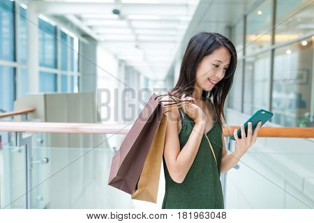 Shopping woman holding paper bag and using mobile phone