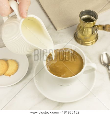 Milk poured into a cup of coffee, with a vintage coffee pot in the background, and Danish butter cookies. Square photo, selective focus, place for text