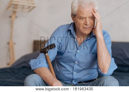 Lots to think about. Pensive cheerless aged man holding a walking stick and holding his head while being involved in his thoughts