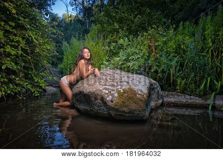 sexy topless woman in the river leaning on a rock