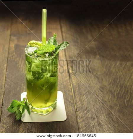 A square photo of a mojito cocktail with mint leaves, a wedge of lime, and a drinking straw, on a dark wooden background with copyspace