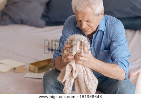 Painful memories. Sad unhappy senior man sitting in the bedroom and holding his wifes knitted jacked while grieving about her