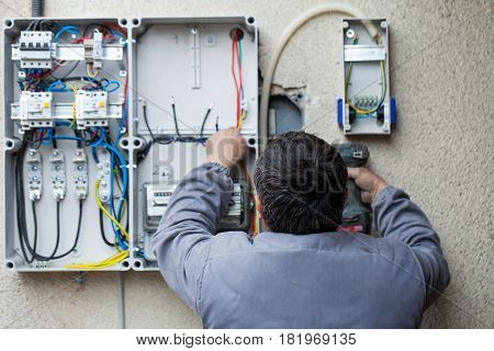 Picture of an electrician fixing an electric fuse at home
