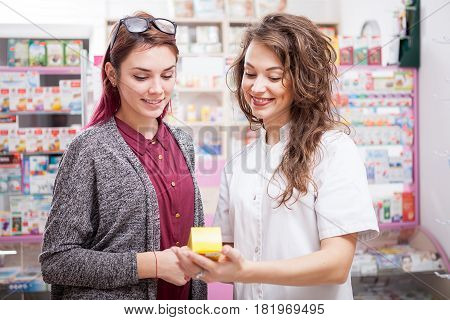 Pharmacist and her client in front of the desk. Healthcare business