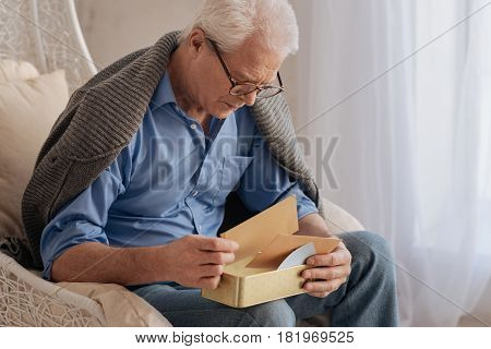 Sweet memories. Sad nice elderly man turning over his old letters and remembering his youth while being alone
