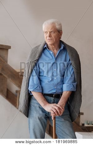 Being in depression. Cheerless depressed senior man leaning on the walking stick and feeling unhappy while standing in the middle of the room