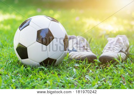 Football On Green Grass And Stud Shoe With Sun Light