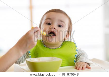 Baby eating food with mother help at home