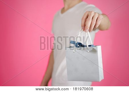 Man Holding In Hand Blank Blue Paper Gift Bag Mock Up. Empty Package Mockup Hold In Hands Isolated.
