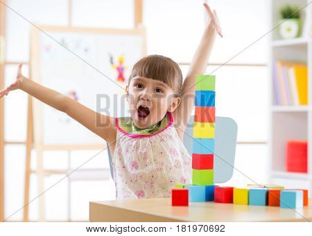 happy kid playing with block toys in day care center