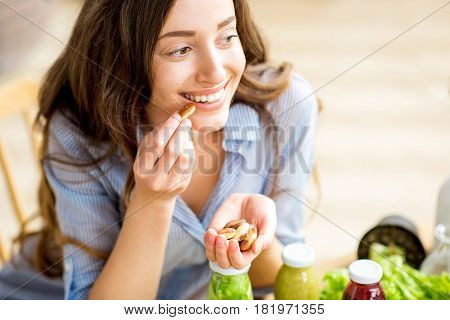 Closeup view from above of a woman eating brasil nuts with healthy food on the background