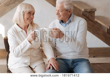 Its tea time. Positive delighted cheerful couple looking at each other and clinking cups while having tea together
