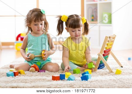 Children playing together with building blocks. Educational toys for preschool and kindergarten kids. Little girls build pyramid toys at home or daycare.