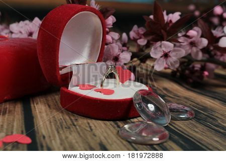 Engagement ring.Will you marry me?Red box with ring and cherry plum branch.